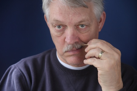 toothpick: older man cleans his teeth with a toothpick Stock Photo