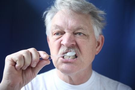 年配の男性は、彼の歯をブラシします。