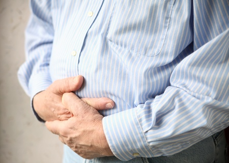 a man holds both hands to his stomach Stock Photo