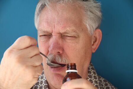 frowns: sick man frowns as he takes a spoonful of cough syrup Stock Photo