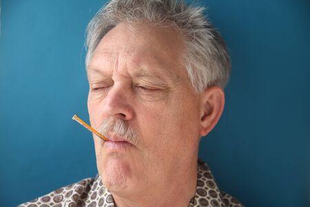 sick older man checks his temperature Stock Photo - 12609943