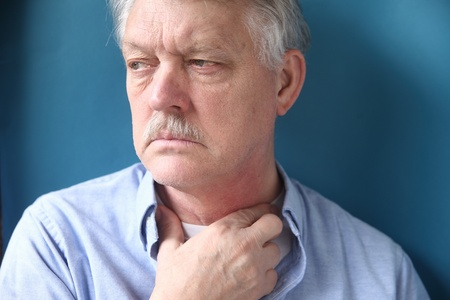 swallowing: senior man with throat or neck irritation Stock Photo