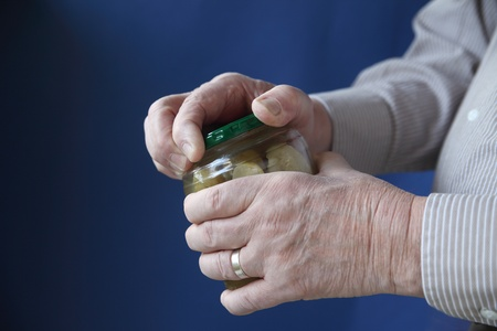 an older man struggles to open a jar of pickles