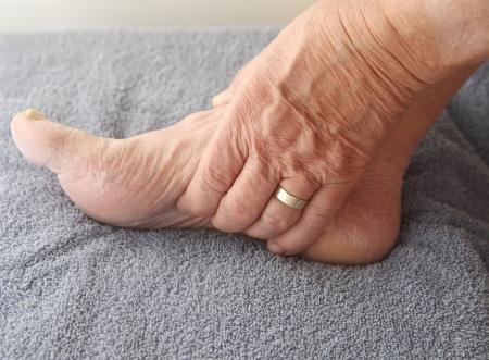 foot pain: man tends to his aching arch Stock Photo