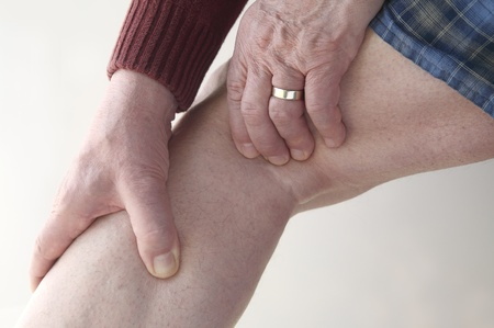 calf strain: a man has soreness in the back of his knee and calf Stock Photo