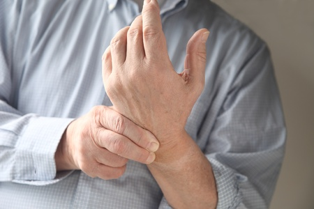 businessman checks the soreness in his wrist