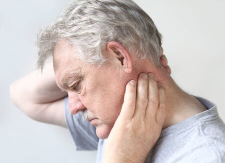 senior man on a neck pain: man tries to move his stiff, painful neck