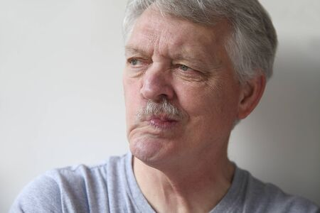 wry: an older man twists his mouth to one side