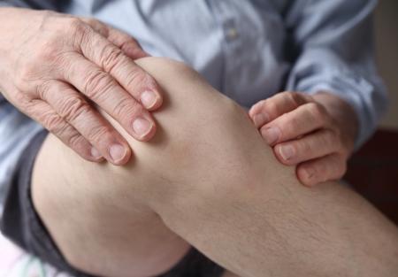 아픈: 고통스러운 무릎 관절에 자신의 손을 가진 남자 스톡 사진