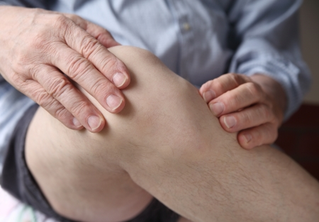 a man with his hands on a painful knee joint photo