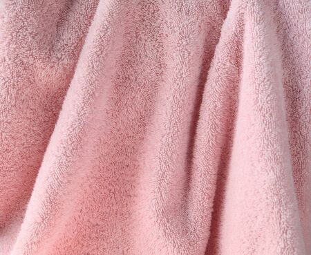 terry: a large pale pink bath towel close up