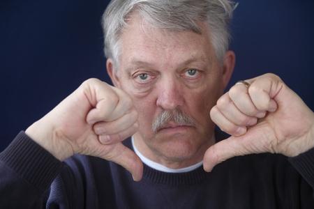 comunicacion no verbal: un hombre más viejo con ambas pulgares hacia abajo