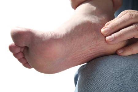 foot pain: a man tends to his aching foot
