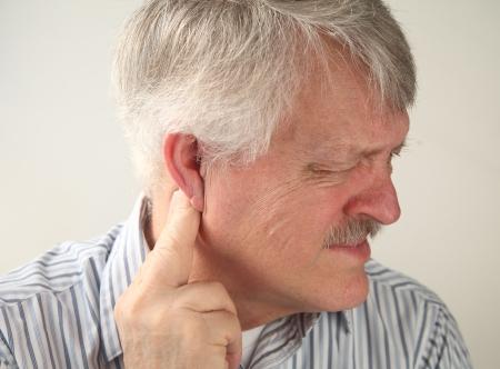 dolor de oido: hombre mayor sufre de presi�n detr�s de la oreja Foto de archivo