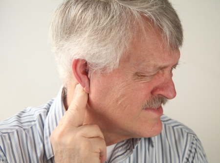 senior man suffers from pressure behind his ear Stock Photo
