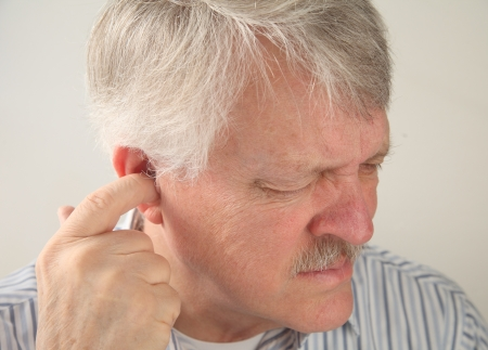dolor de oido: un hombre mayor trata de aliviar el dolor profundo en la oreja