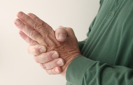 health concern: a man tries to massage the numbness out of his hand