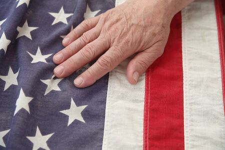 a man s hand on a very old American flag photo