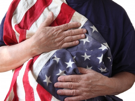 a man holds the American flag close to his body photo