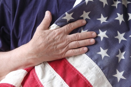 a man s hand on a USA flag against his chest