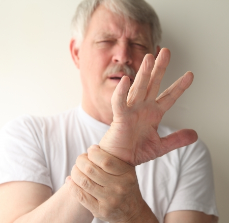 a senior man winces at the pain in his hand Stock Photo