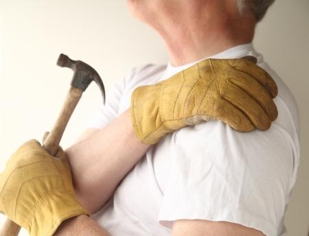그의 다른 손으로 망치를 들고있는 동안 남자는 자신의 아픈 어깨를 파악 스톡 콘텐츠