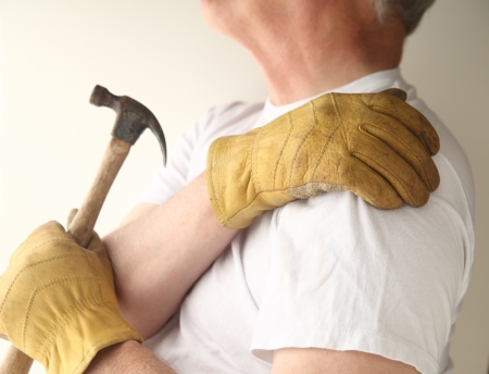 a man grasps his aching shoulder while holding a hammer with his other hand