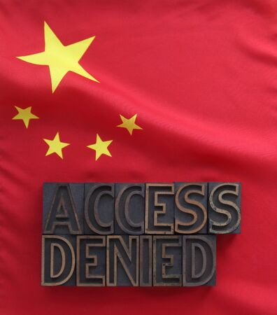 censorship: the words access denied in old wood type on a Chinese flag