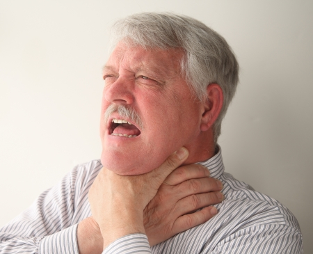 a senior man with food stuck in his throat
