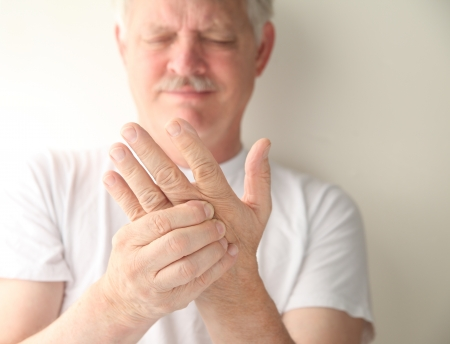 an older man has numbness and tingling in his hand photo