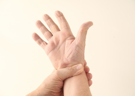 a man grips his painful wrist photo