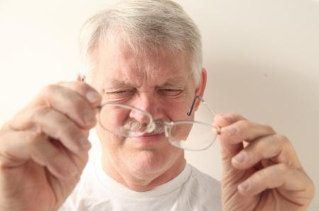 an older man squints at his glasses Banque d'images