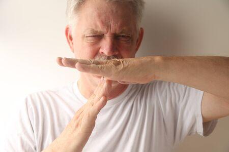 comunicacion no verbal: un hombre mayor que le da el gesto de tiempo de espera