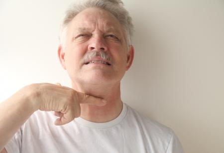 comunicacion no verbal: un hombre mayor que da la se�al de cutthroat Foto de archivo