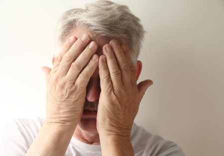 embarrassment: an older man hides his face in embarrassment or grief