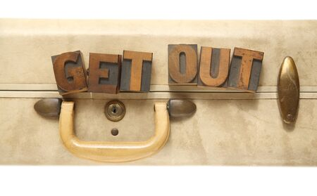 get out: the words get out in old letterpress wood type on an old suitcase