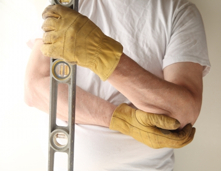 a man holds a level in one hand and tends to his painful elbow with the other