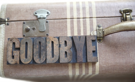 the word goodbye in old letterpress wood type on an old suitcase