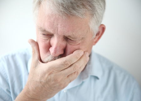 senior man holds his hand to his mouth while feeling nauseous Stock Photo
