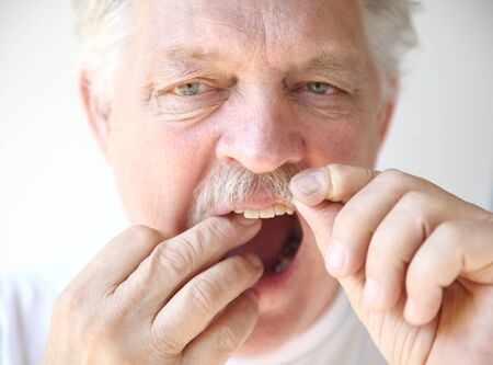 flossing: front view of an older man practicing good dental hygiene Stock Photo
