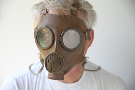 older man wearing an old gas mask Stock Photo