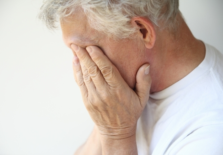 grieving: senior man covers his face with his hands
