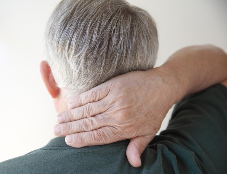 senior man on a neck pain: rear view of a man putting his hand on his aching neck Stock Photo