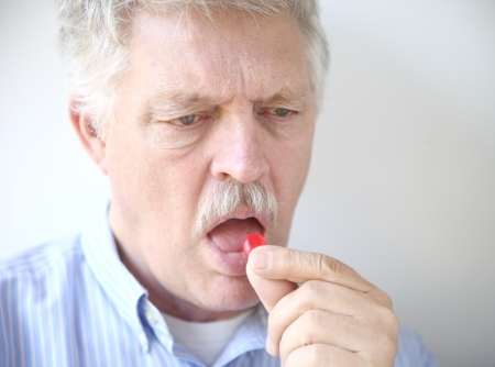 lozenge: an older man takes a throat lozenge for a sore throat Stock Photo