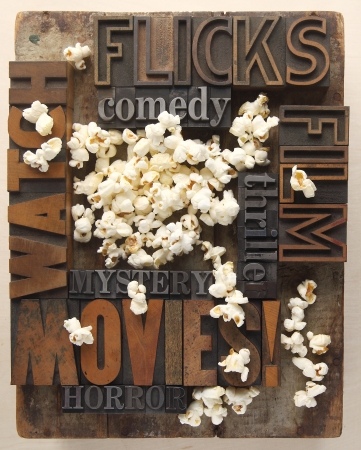 words associated with movie watching in old letterpress wood and metal type with popcorn