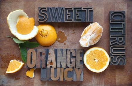 letterpress letters: a navel orange with peeled, halved, and cut sections and descriptive words with spilled juice on a cutting board