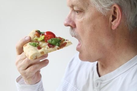 senior man set to bite into a slice of bacon, lettuce and tomato pizza