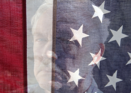 an older man is seen behind an American flag Stock Photo