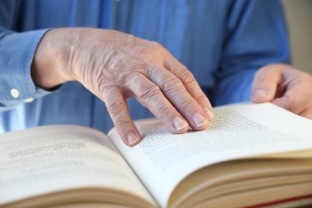 a senior man s hands on a book