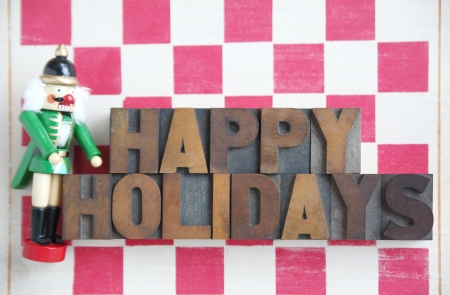 the nutcracker: a nutcracker with the words  happy holidays  in wood type on a stenciled checkerboard